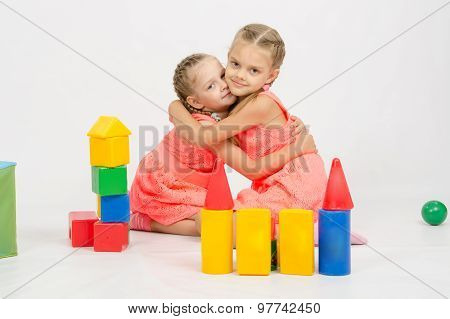 Happy Two Girls Embrace Building A Castle Out Of Blocks