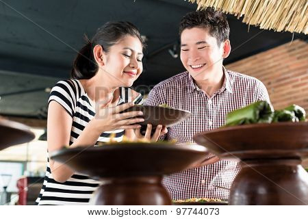 Asian woman and man choosing food at Indonesian buffet in restaurant