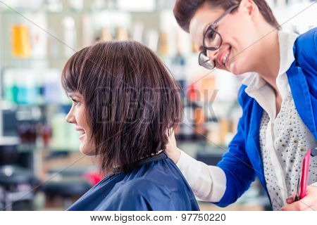 Female coiffeur cutting women hair in hairdresser shop poster