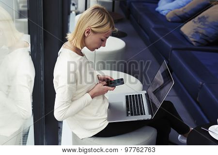 Female freelancer connecting to wireless via smart phone while sitting in modern coffee shop