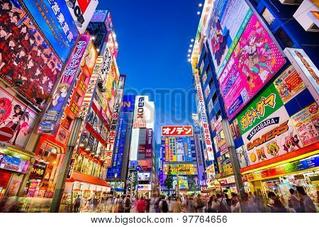 TOKYO, JAPAN - AUGUST 1, 2015: Crowds pass below colorful signs in Akihabara. The historic electronics district has evolved into a shopping district for video games, anime, manga, and computer goods.