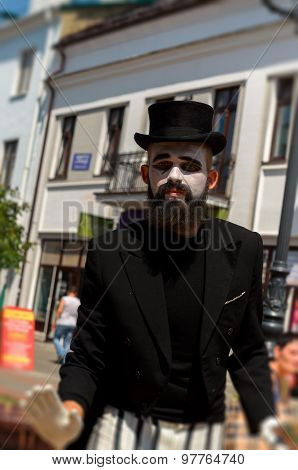 Mime on the street in a black hat.