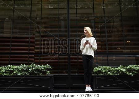 Full length portrait of gorgeous young woman holding smartphone in the hand and looking away