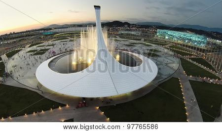 RUSSIA, SOCHI -?? JUL 27, 2014: Fountain with illumination near sports stadium Iceberg and Adler-arena at summer evening. Aerial view. (Photo with noise from action camera)