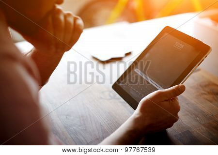 Thoughtful business man looking to the digital tablet screen while sitting at wooden table