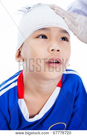 Athlete little asian (thai) boy in blue sportswear with trauma of the head. Doctor makes a bandage on head patient. Child unhappy on white background poster