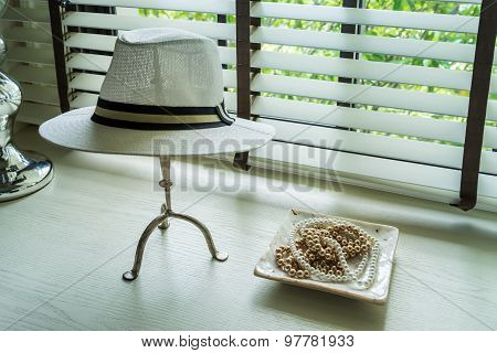 White Hat And Jewelry Set On A Dresser Table In A Contemporary Room.