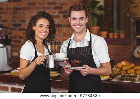Portrait of waiter and waitress smiling at camera at coffee shop