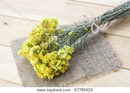 Dwarf everlast flowers bouquet and napkin on light wooden table