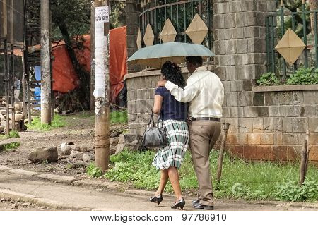 A Couple Walking On The Streets Of Addis With An Umbrella