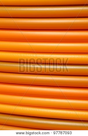 long coils of orange plastic pipes for the installation of underground utilities and energy of optical fibers poster