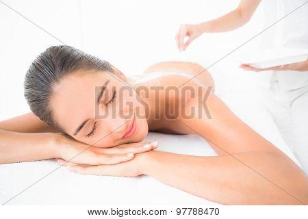 Beautiful brunette enjoying a salt scrub treatment at the health spa poster