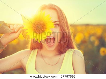 Beauty joyful teenage girl with sunflower enjoying nature and laughing on summer sunflower field. Sunflare, sunbeams, glow sun. Backlit.