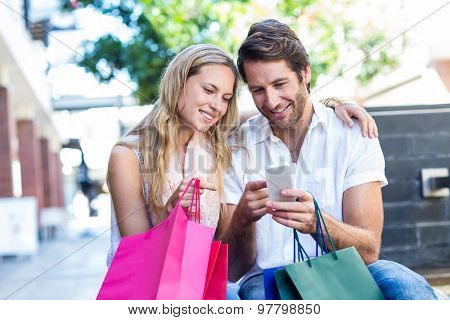 Smiling couple with shopping bags sitting and using smartphone at shopping mall