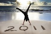 happy new year 2011 on the beach of sunrise . young man handstand and celebrate . poster