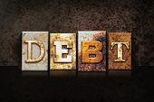 "The word ""DEBT"" written in rusty metal letterpress type on a dark textured grunge background. poster"