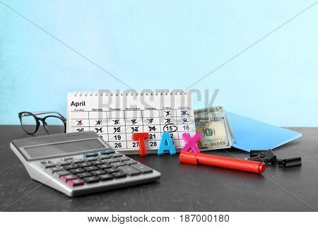 Calendar, word TAX and calculator on table