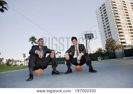 Businessmen sitting on basketballs on basketball court