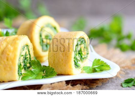 Cheese and greens omelet rolls on a plate. Homemade fried omelet rolls with grated cheese and finely chopped greens. Healthy low carb recipe. Rustic style. Closeup