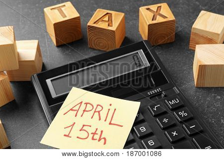 Wooden cubes with word TAX, note and calculator on table