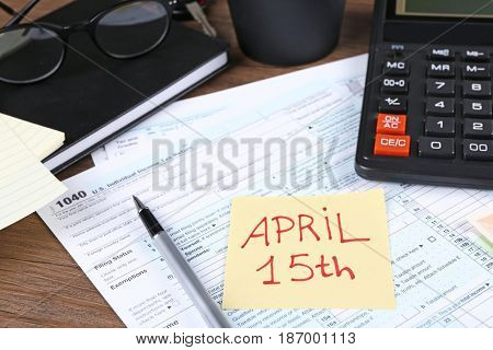 Paper note with text APRIL 15TH, forms and calculator on table