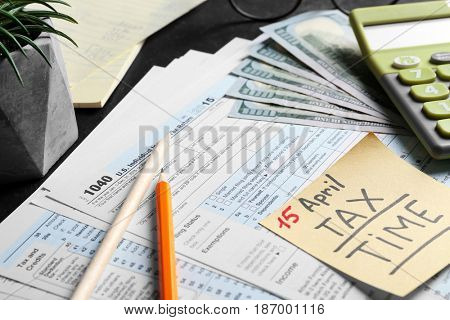Paper note with text 15 APRIL TAX TIME,  form and calculator on table