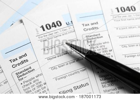 Individual Tax Return Forms and pen on table