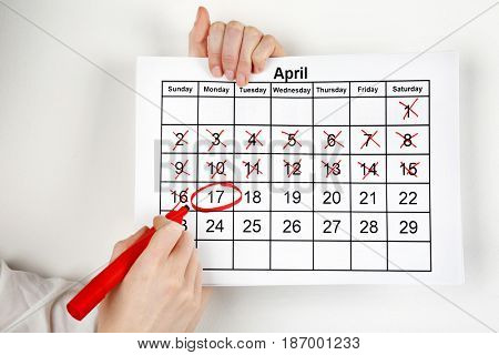 Woman marking date in calendar on white wall background