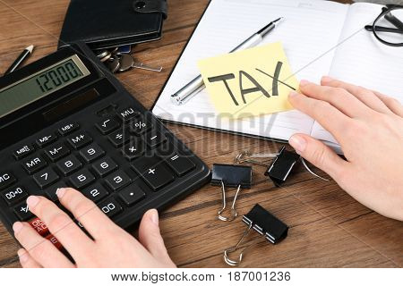 Woman sitting at table with calculator and notebook