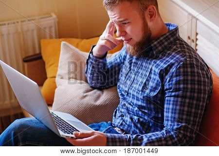 Young Man Working Absorbed On Laptop At Home