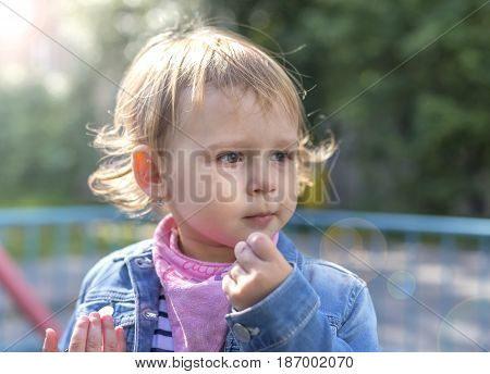 Beautiful gentle thoughtful little girl in the sunny day. Portrait.