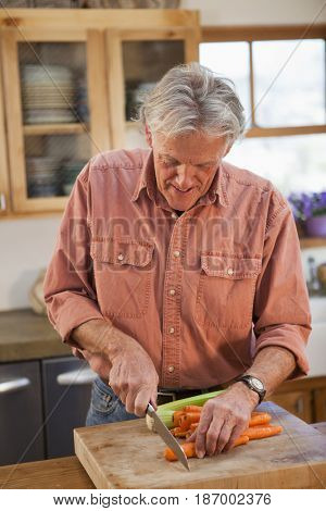 Caucasian man cutting carrots