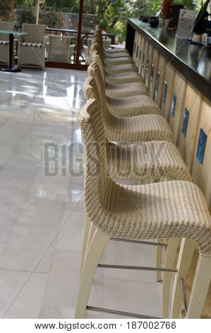 Bar with white stools plaiting with plastic straps