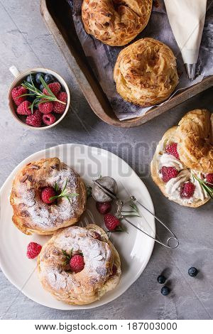 Filling and empty homemade choux pastry cake Paris Brest with raspberries, almond, sugar powder, rosemary on plate and oven tray with berries over gray texture background. French dessert. Flat lay