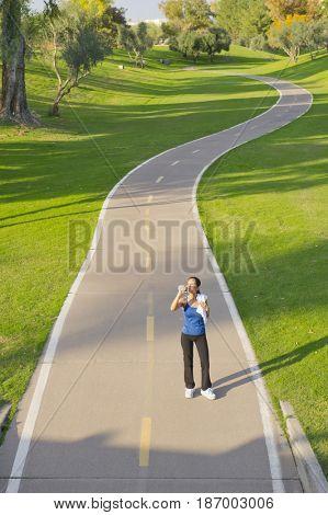 Hispanic woman drinking water on path