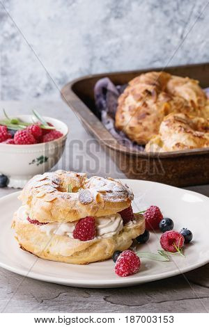 Filling and empty homemade choux pastry cake Paris Brest with raspberries, almond, sugar powder, rosemary on plate and oven tray with berries over gray texture background. French dessert.