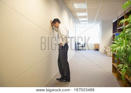 Frustrated Caucasian businessman leaning on office wall
