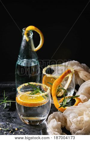 Tonic water cocktail with rosemary and orange. Two glasses and bottle with zest sugar and bubbles with textile gauze over black texture background. Refreshing beverage alco non alcohol