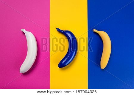 Close-up View Of White, Blue And Yellow Bananas Isolated On Pink, Yellow And Blue