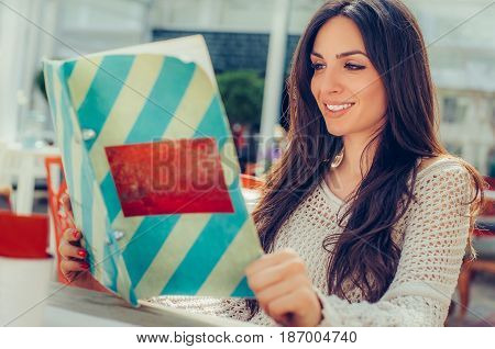 Beautiful Woman Looking At Menu And Ordering Foods In Restaurant