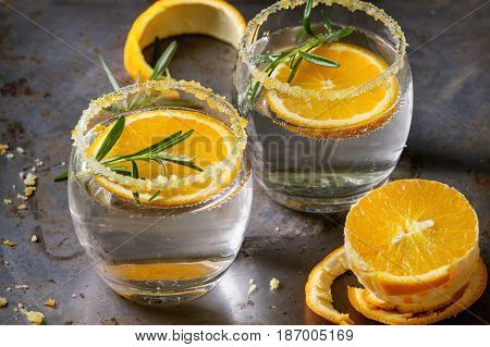 Tonic water cocktail with rosemary and orange. Two glasses with zest sugar and bubbles with textile over dark texture metal background. Refreshing beverage alco non alcohol