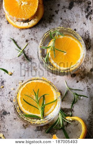 Tonic water cocktail with rosemary and orange. Two glasses with zest sugar and bubbles with textile over dark texture metal background. Refreshing beverage alco non alcohol. Top view