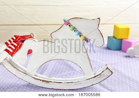 Composition with baby name bracelet on wooden background