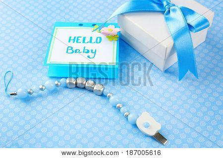Pacifier clip for baby, greeting card and gift box on table