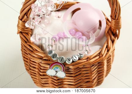 Bracelet with baby name Olivia in basket on white background