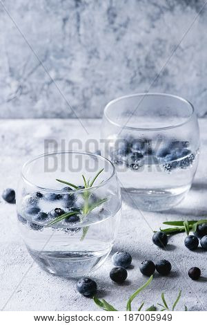 Tonic water cocktail with rosemary and blueberries. Two cold glasses over gray blue texture background. Refreshing beverage alco non alcohol