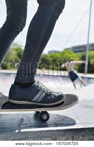 closeup of a young caucasian man skateboarding in an outdoors skate park