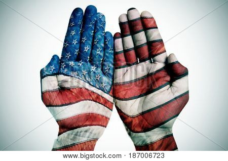 the hands of a young caucasian man put together patterned with the flag of the United States on an off-white background, with a slide vignette added
