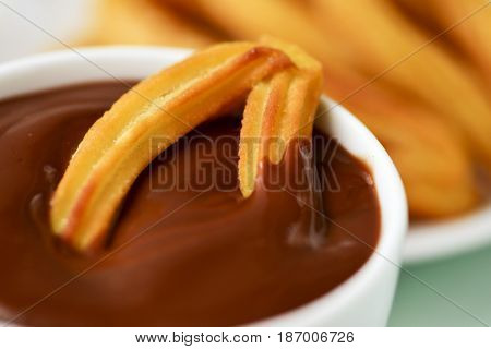 churros con chocolate, a typical Spanish sweet snack, on a table