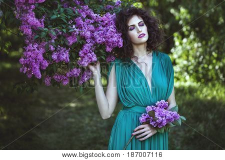 Woman luxuriates in lilac bushes she closes her eyes and inhales the fragrance of flowers.
